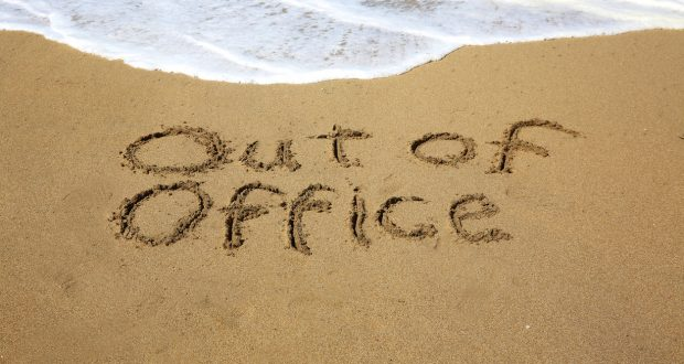 Out of office, a message written in the sand at the beach.